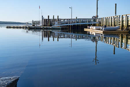 Public pier plus boats and dinghies on a floating dock on Penobscot Bay at Searsport, Maine in the early morning light. Foto de archivo