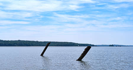 The ruins of an old pier in the water at Stockton Harbor in Maine with a blue sky above and a distant sailboat.