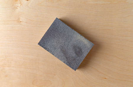 Top close view of a sanding sponge atop a piece of birch plywood. Stock Photo