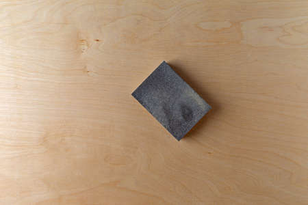 Top view of a sanding sponge atop a piece of birch plywood.