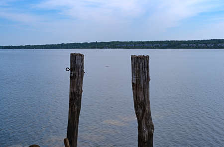 The ruins of an old pier in the water with two posts at Stockton Harbor in Maine with a blue sky above and a distant sailboat. Stock Photo