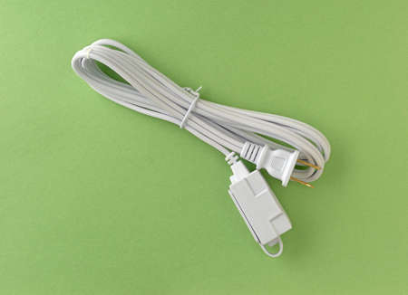 Top view of a new white extension cord on a green paper background.