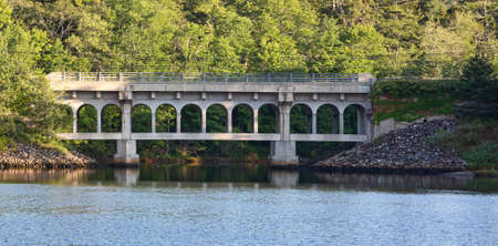 Distant view of an old bridge with cracked concrete on a tidal river on the coast of Maine. Stock Photo