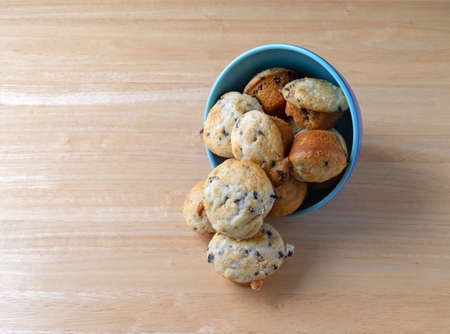 Several freshly baked bite size blueberry muffins a blue bowl on its side spilling onto a wood table. Stock Photo