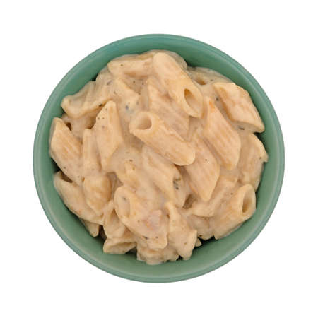Top view of a bowl of pasta with chicken in an alfredo sauce isolated on a white background.