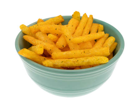 Side view of a serving of cheddar flavored snacks in the shape of a french fries in a green bowl isolated on a white background.
