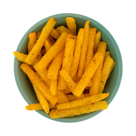 Top view of a serving of cheddar flavored snacks in the shape of a french fries in a green bowl isolated on a white background.