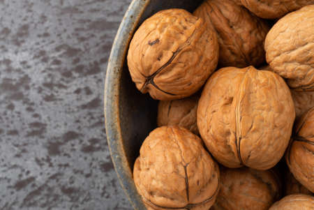 Top close view of an old stoneware bowl filled with walnuts on a gray counter top illuminated with natural lighting.