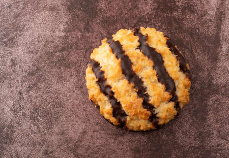 Overhead view of a single dark chocolate striped coconut macaroon on a maroon background illuminated with natural lighting.