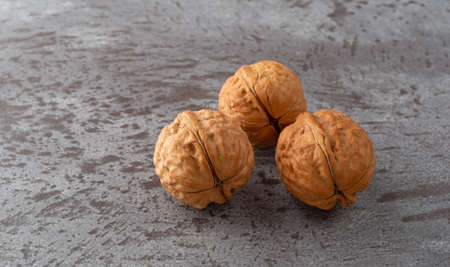 Side view of three whole walnuts atop a gray counter top illuminated with natural lighting. Imagens