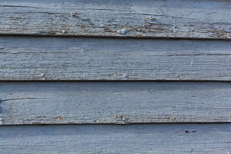 Rows of wood siding with badly peeling blue paint. Stock Photo