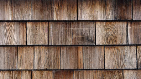 Rows of naturally stained brown wood cedar shingles.