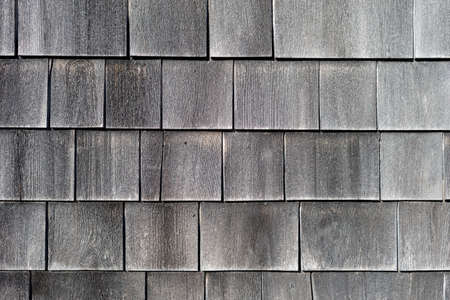 Rows of naturally graying wood cedar shingles.