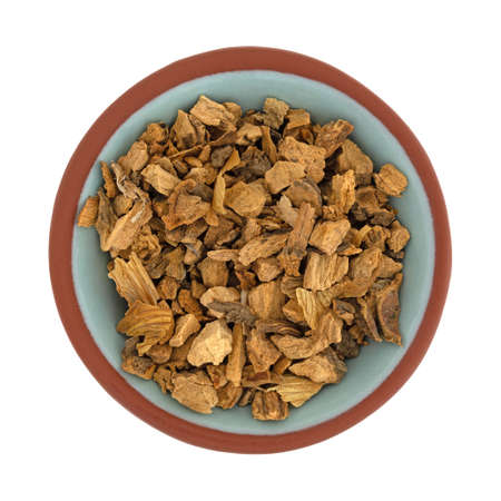 Top view of a small bowl filled with organic cut gentian root isolated on a white background.