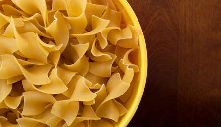 Top close view of a bowl filled with no yolk wide pasta atop a wood table. Stock Photo