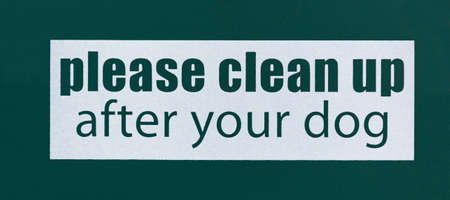 Green and white lettering please clean up after your dog sign. Reklamní fotografie
