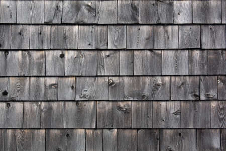 Rows of naturally graying wood cedar shingles in the early morning light. Stock Photo