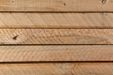 Top view of the surface of several rough sawn lumber boards.