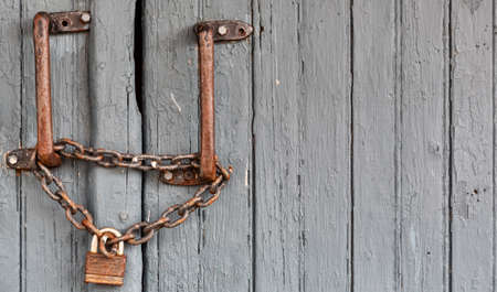 A very old padlock and chain attached to iron hand bars attached to a wood sliding door. Stock Photo