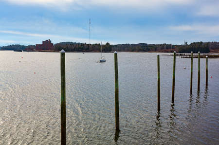 Old wood pilings with a sailboat in the distance at Wiscasset Maine in the late fall.