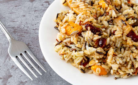 Close view of chicken with pecans and wild rice on a plate with a fork to the side on a gray background illuminated with natural lighting.