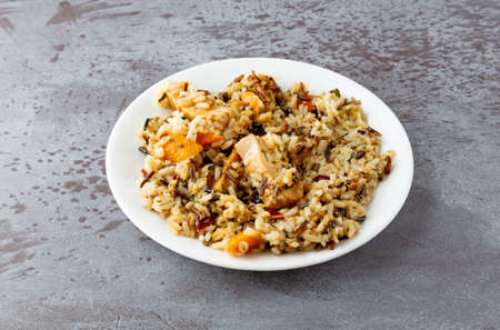 Chicken with pecans and wild rice on a plate on a gray background illuminated with natural lighting.