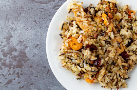Overhead close view of chicken with pecans and wild rice on a plate atop a gray background illuminated with natural lighting. Stock Photo