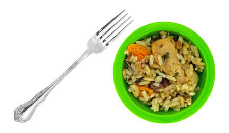 Chicken with pecans and wild rice in a small green bowl with a fork to the side isolated on a white background. Stock Photo