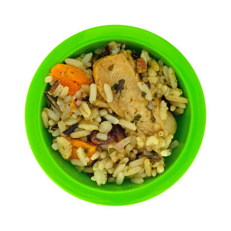 Overhead view of chicken with pecans and wild rice in a small green bowl isolated on a white background.