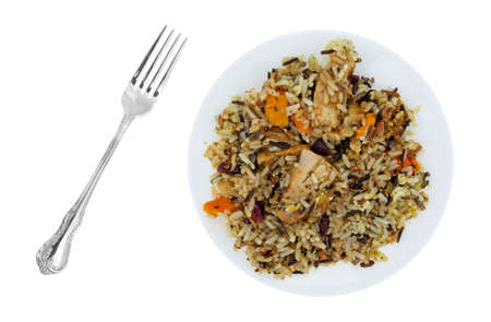 Overhead view of chicken with pecans and wild rice on a plate with a fork to the side isolated on a white background. Stock Photo
