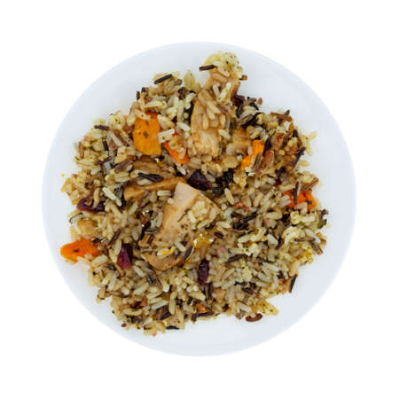 Overhead view of chicken with pecans and wild rice on a plate isolated on a white background.