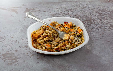 Side view of a chicken with pecans and wild rice TV dinner in a plastic tray with a fork to the side on a gray background illuminated with natural lighting.