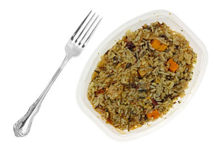 Overhead view of a chicken with pecans and wild rice TV dinner in a plastic tray with a fork to the side isolated on a white background.