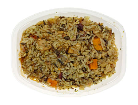 Overhead view of a chicken with pecans and wild rice TV dinner in a plastic tray isolated on a white background.