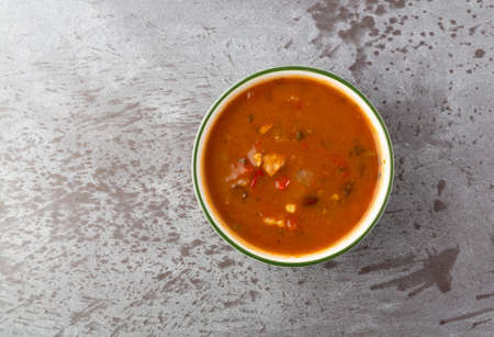 Overhead view of a bowl of chicken tortilla soup on a gray background. Stock Photo