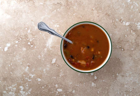 Overhead view of a bowl of chicken tortilla soup with a spoon in the food on a marble table top. Stock Photo