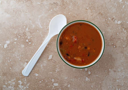 Overhead view of a bowl of chicken tortilla soup with a white plastic spoon to the side on a marble table top.