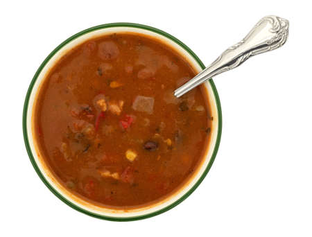 Overhead view of a bowl of chicken tortilla soup with a spoon in the food isolated on a white background.