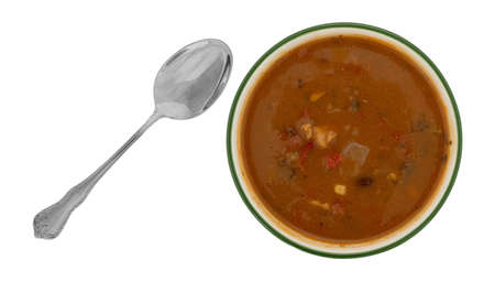 Overhead view of a bowl of chicken tortilla soup with a spoon to the side isolated on a white background. Stock Photo