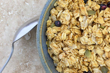 Top close view of a bowl of dry organic breakfast cereal with dried blueberries and pumpkin seeds plus a spoon in the food on a marble table.