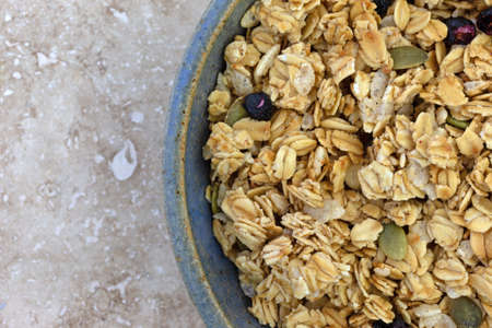 Top close view of a bowl of dry organic breakfast cereal with dried blueberries and pumpkin seeds on a marble table.