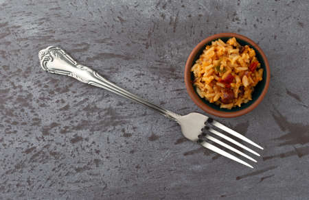 Overhead view of a small bowl of Mexican rice and beans with a fork to the side on a gray background illuminated with natural lighting.