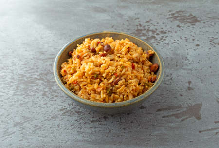 Side view of a bowl of Mexican rice and beans on a gray background illuminated with natural lighting. Stock Photo