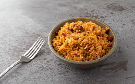 Side view of a bowl of Mexican rice and beans with a fork to the side on a gray background illuminated with natural lighting. Stock Photo