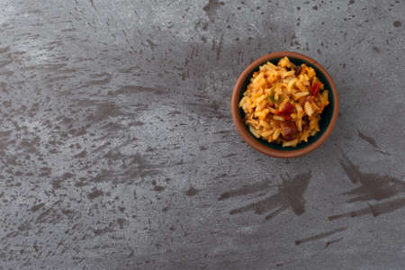 Overhead view of a small bowl of Mexican rice and beans offset on a gray background illuminated with natural lighting.