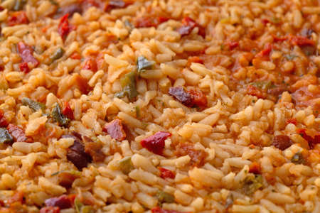 Close side view of cooked Mexican rice and beans in a skillet illuminated with natural lighting.