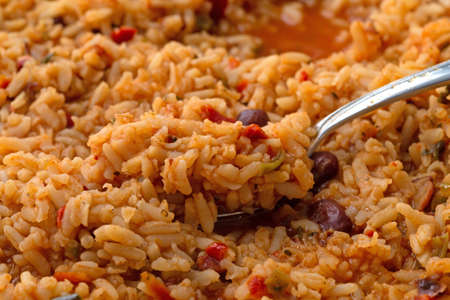 Close side view of cooked Mexican rice and beans in a skillet with a heaping spoonful of food illuminated with natural lighting.
