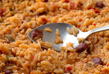 Close side view of cooked Mexican rice and beans in a skillet with a spoon on the food illuminated with natural lighting. Stock Photo