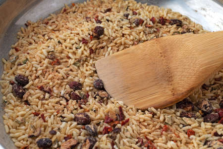 Side view of Mexican rice and beans dry mix in a skillet cooking with a wood spoon in the food illuminated with natural lighting.