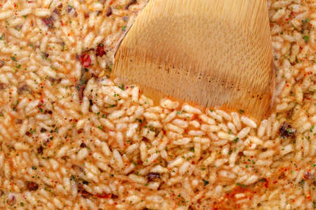 Side view of Mexican rice and beans mix in a skillet cooking with a wood spoon in the food illuminated with natural lighting. Stock Photo